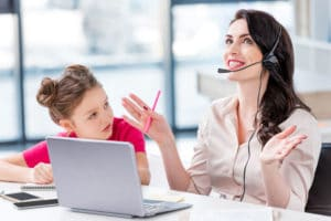little girl looking at happy mother in headset working in office